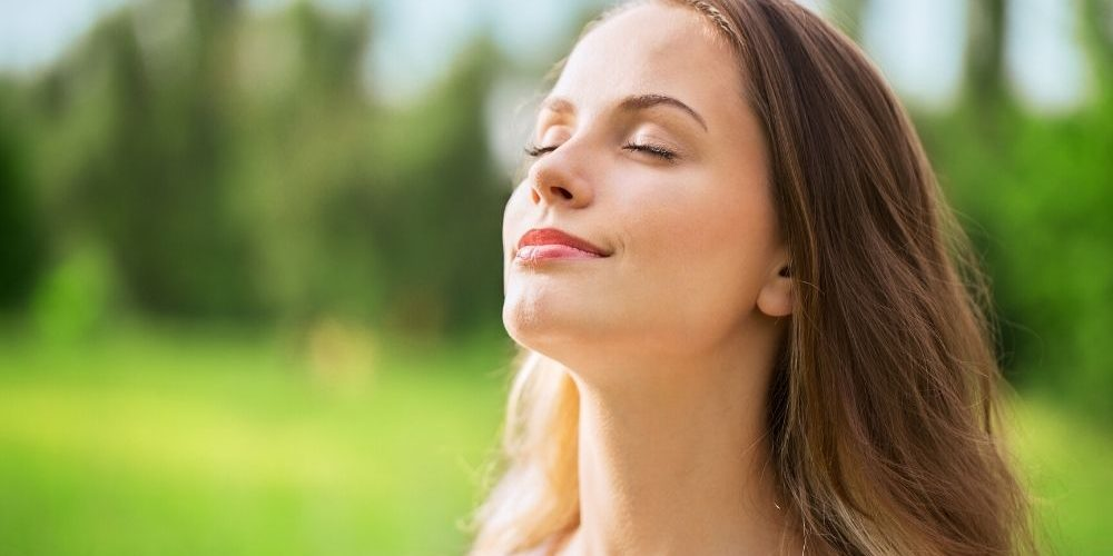 A close up of a woman breathing in the nature | Feature | How Can I Clean My Lungs? | Lung Detox