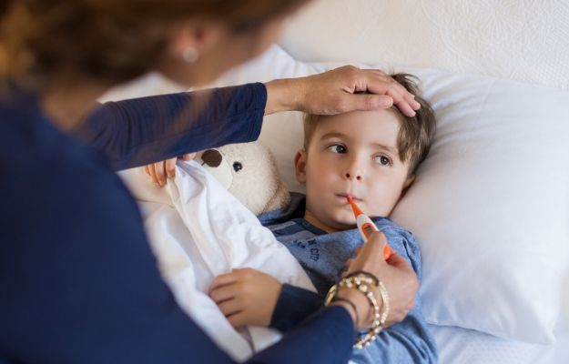 A mom taking care of her son who is having a fever on the bed | How Do I Know If My Child's Cough Is Serious? |
