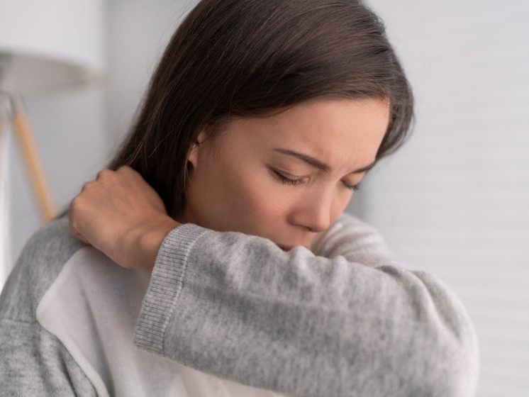 A young woman covering nose and mouth when coughing and sneezing with tissue or flexed elbow | Feature | Cough Frequency: What Do We Know?
