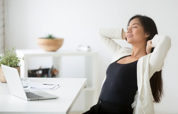 Relaxed happy asian woman enjoying break at workplace | How to Breathe Better for More Energy | How To Breathe Better: 4 Breathing Exercises Anyone Can Do
