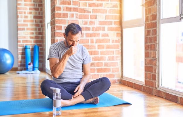 Sportman sitting on mat doing stretching yoga exercise at gym feeling unwell and coughing | Why Do I Cough After Exercise? | Cough Frequency: What Do We Know?