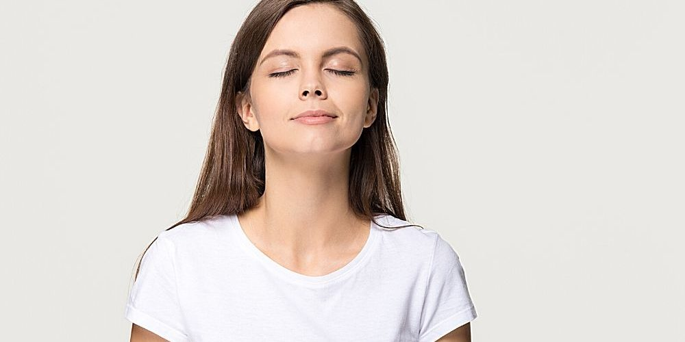 Young woman taking deep breath feel   feature   How To Breathe Better: 4 Breathing Exercises Anyone Can Do
