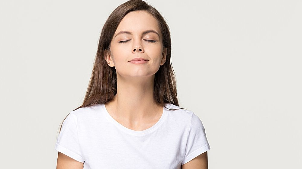 Young woman taking deep breath feel | feature | How To Breathe Better: 4 Breathing Exercises Anyone Can Do
