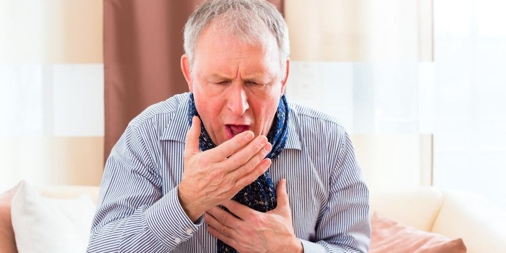 an old man is coughing and take his hands to cover mouth   Feature   Coughing After Eating   What Does It Mean?