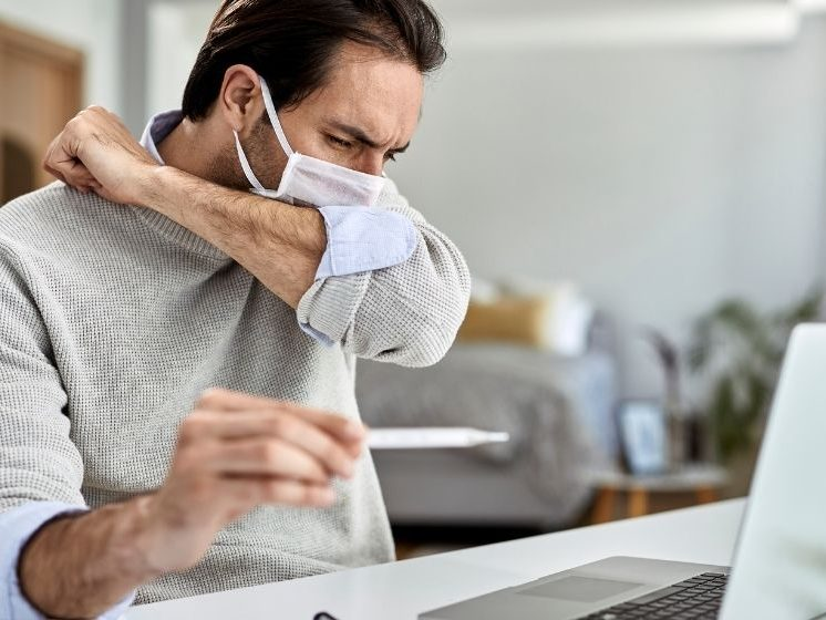 Sick guy with protective face mask sneezing into elbow | Feature | Why Cough Tracking Is A Valuable Diagnosis Tool