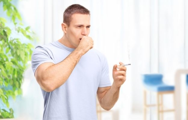 a man is coughing while holding a cigarette while | What Causes a Chronic Cough?