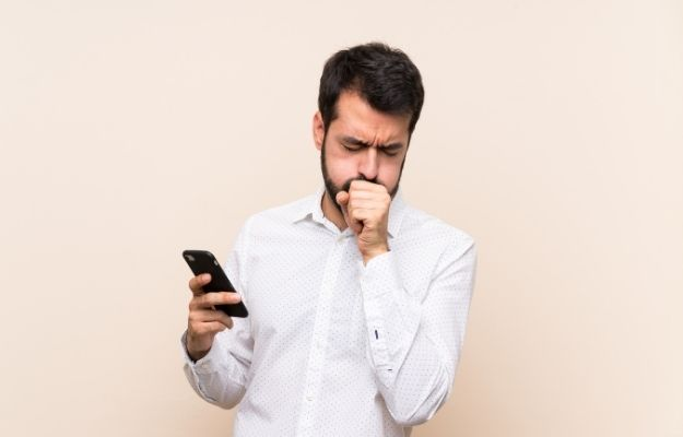 a man is coughing while holding a phone | Hyfe's Core Values | Hyfe App: Diagnostics For Everyone