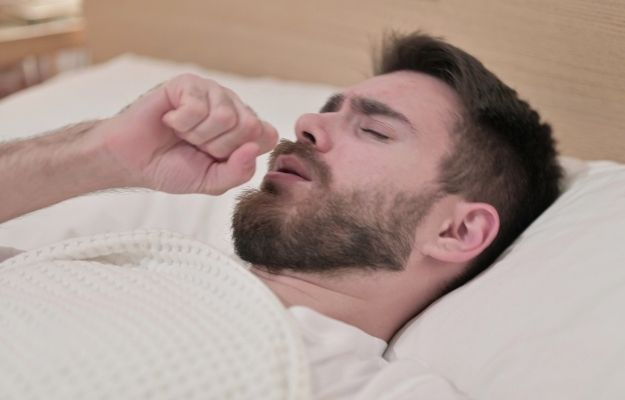 a man lying on bed and coughing | Why Is My Cough Worse at Night? | Why Is My Cough Worse At Night?