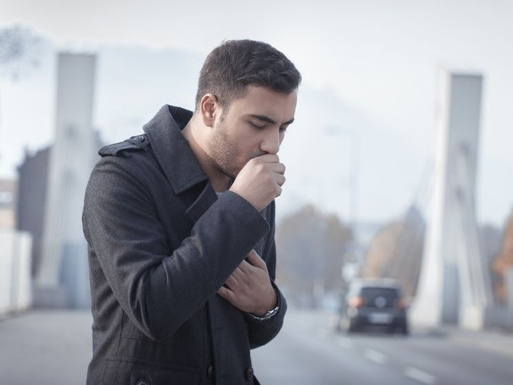 a man wearing black is coughing on the street | Feature Imgage | How To Identify Cough Correlation and Track Your Cough