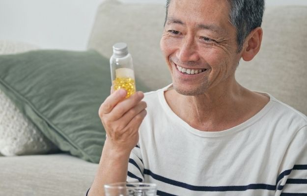 Middle aged asian man taking supplements - ss | How To Boost Immune System During Flu Season | Your Immune System as You Age