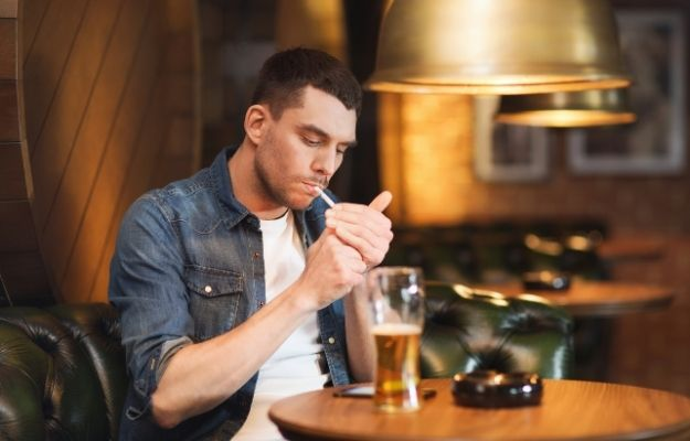 a man smoking and drinking beer in a restaurant - ca | How To Identify Trends and the Good and Bad Habits In Your Life | Ways to Identify Trends: Bad Habits and Health Barriers