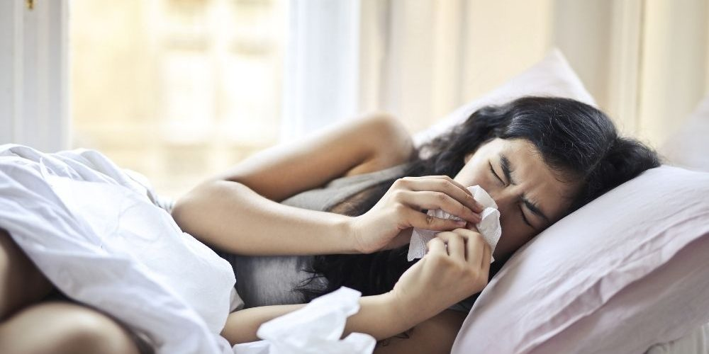 a woman lying on bed is sneezing | COVID or Flu? How to Track Your Health This Flu Season | Feature