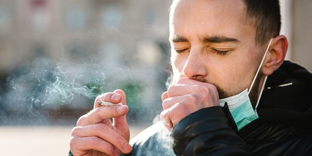 a man is coughing while smoking - ss - featured image | Smoker's Cough: Symptoms and Causes | Feature