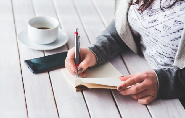 Girl writing in note book - Body H1 - CA | How To Keep A Health Journal To Track Your Cough | What Is A Health Journal and Why Is It Important?