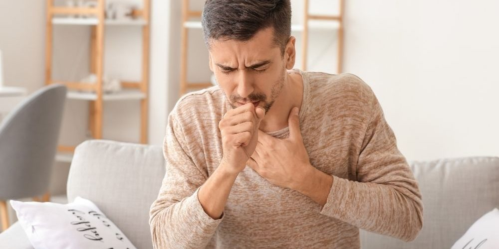 Guy coughing intensively - Feature - CA | What Causes A Chronic Cough? (And How To Kick It) | Feature