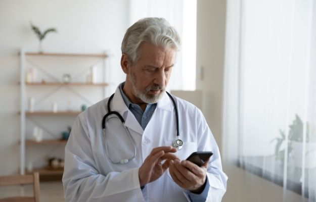 Doctor looking at his phone - How Cough Trackers Detect Pandemic - How Cough Trackers Could Help Detect The Next Pandemic