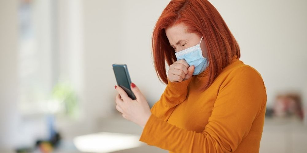 Girl wearing mask coughing while holding her phone   Feature   How Cough Trackers Could Help Detect The Next Pandemic