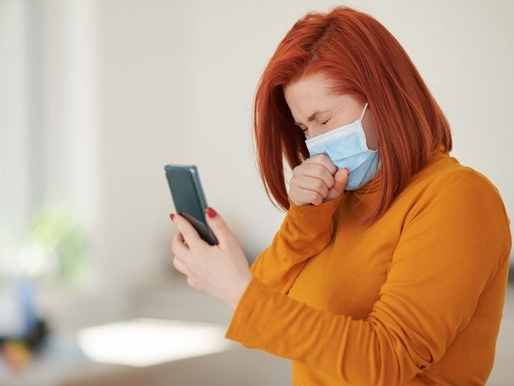 Girl wearing mask coughing while holding her phone | Feature | How Cough Trackers Could Help Detect The Next Pandemic