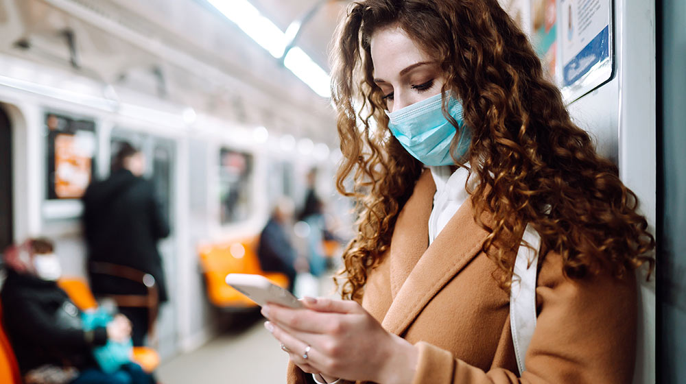 woman wearing mask is checking her phone on subway-feature-ss | The Importance of Tracking Ambient Coughs | feature