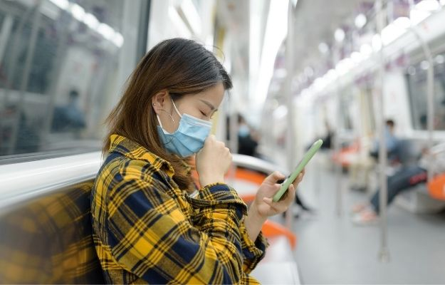 woman wearing yellow button-up shirt is coughing while holding phone-ss | The Importance of Tracking Ambient Coughs | An App to Help with Tracking Coughs