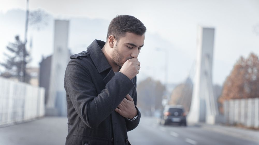 Man in black coat cough while covering his mouth | Feature | What Is a Dry Cough (FAQ + Remedies)