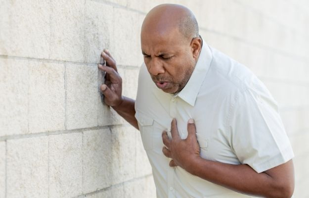 Man in white shirt holding is chest in pain while leaning on a wall - What Are the Symptoms of Restrictive Lung Disease | What Are the Symptoms of Restrictive Lung Disease | Restrictive Lung Disease: What You Need to Know