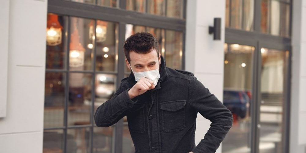 man wearing mask and coughing on the street   feature   How to Get Rid of a Cough in 5 Minutes