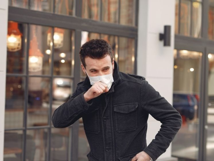 man wearing mask and coughing on the street | feature | How to Get Rid of a Cough in 5 Minutes