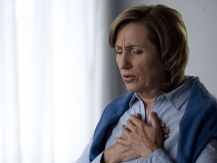 middle-age woman holding her hands against her chest and feeling uncomfortable | Feature | Restrictive Lung Disease: What You Need to Know