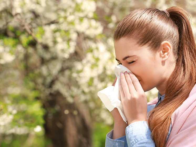 woman sneezing in spring blossom background | Feature | How to Get Rid of Spring Allergies