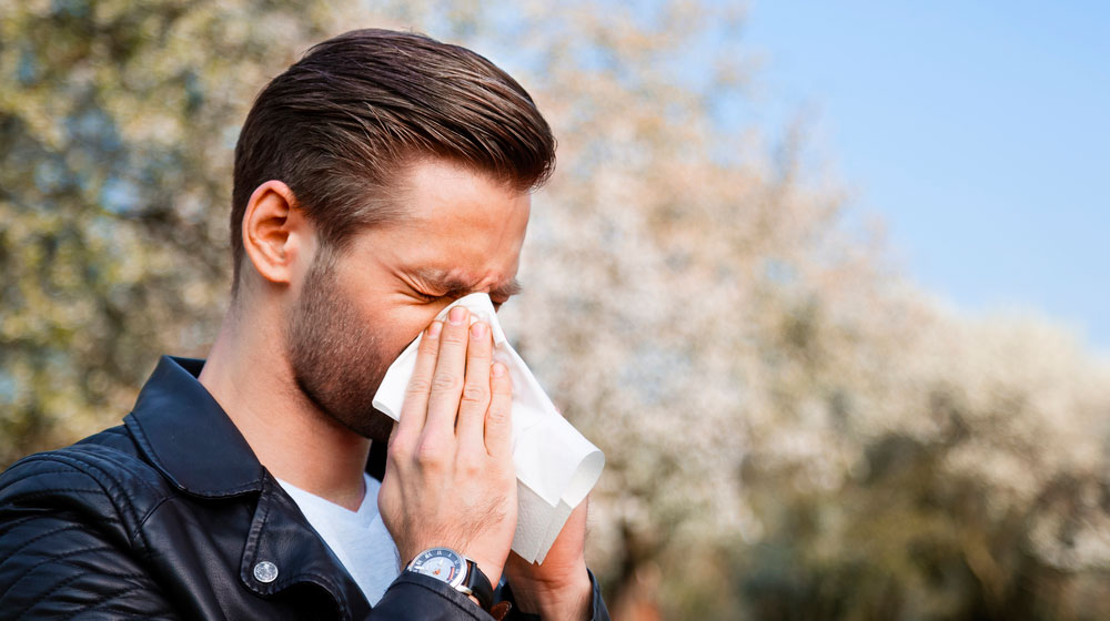young-caucasian-man-sneezing-due-to-pollen-allergy | Feature | All You Need to Know Pollen Allergies
