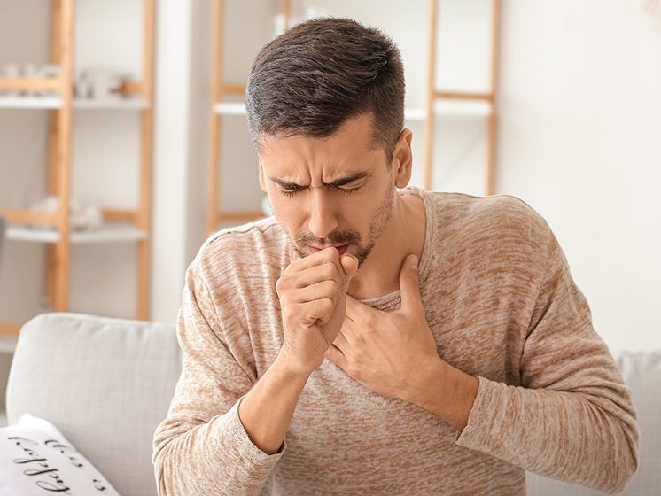 Coughing young man at home|Still Coughing After Covid? Here's What To Do|feature