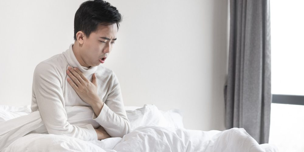 Young man coughing in bed on the early morning   Morning Cough Causes & Symptoms   feature