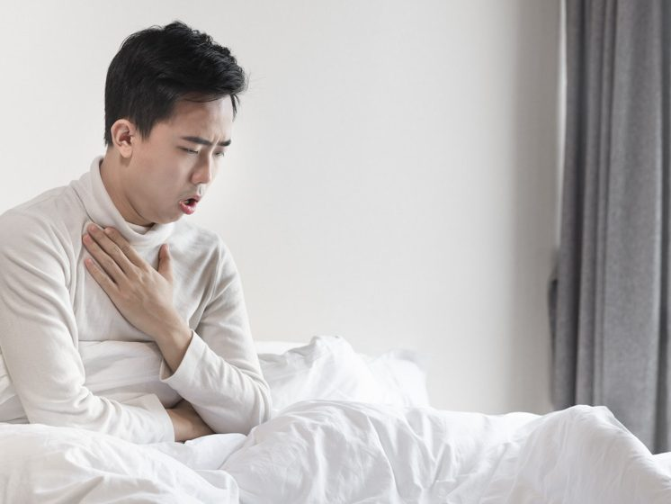 Young man coughing in bed on the early morning | Morning Cough Causes & Symptoms | feature