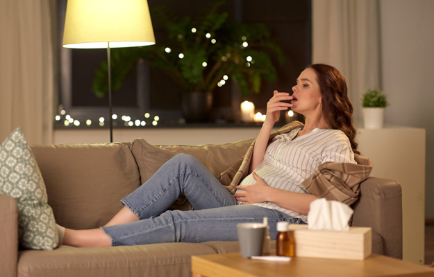 Young pregnant woman coughing on the couch at night | Chronic Cough While Pregnant? This Might Be Why |  Hormones Change Respiratory Function